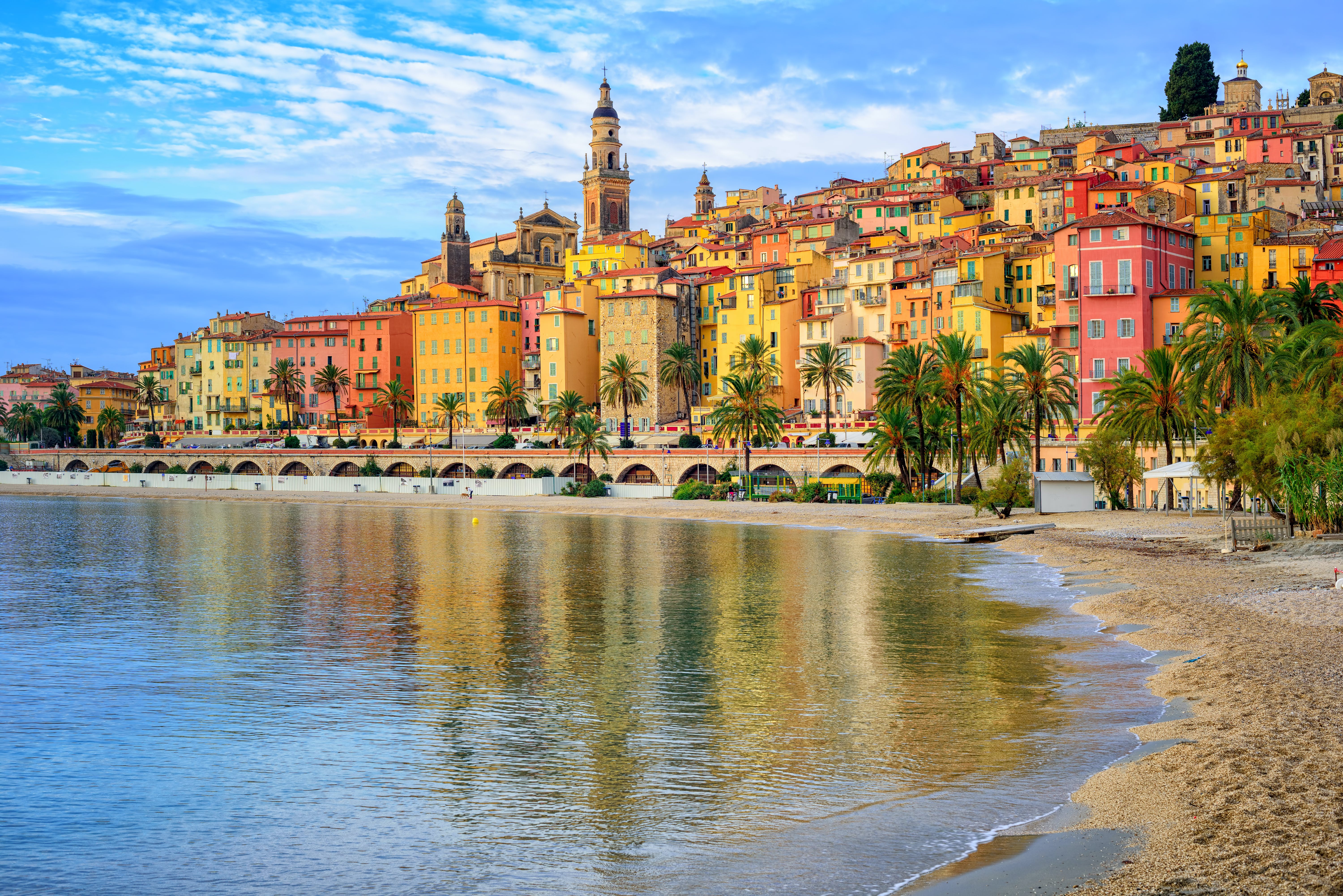Sand beach beneath the colorful old town Menton in Nice on the French Riviera, France.
